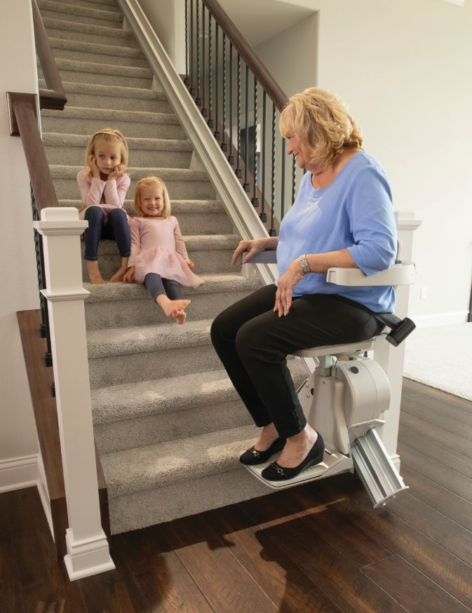 senior woman sitting on stair lift and smiling at grandchildren sitting on the stairs