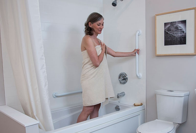 woman using vertically installed grab bar to safely get out of bath tub