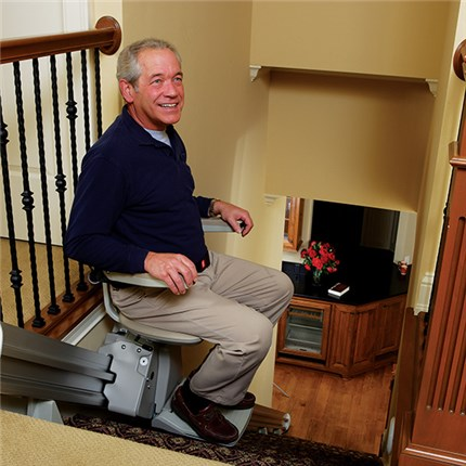 senior man using stair lift to safely get down the stairs