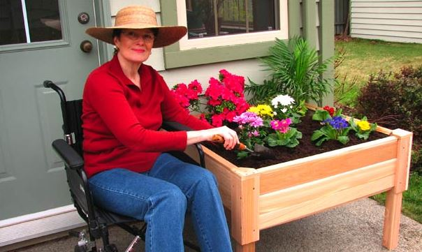 woman in wheelchair planting flowers in her garden