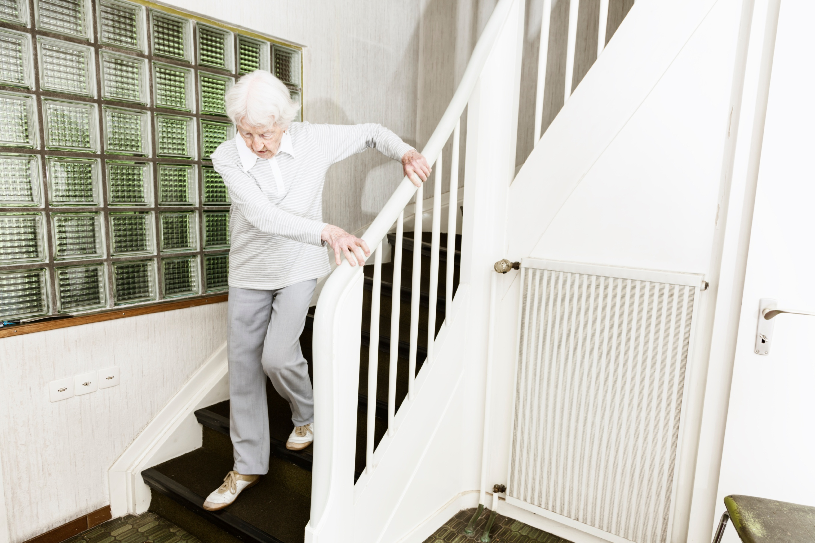 senior woman struggling to get down the stairs in her home