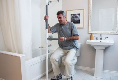 man using safety pole in bathroom to get off of toilet