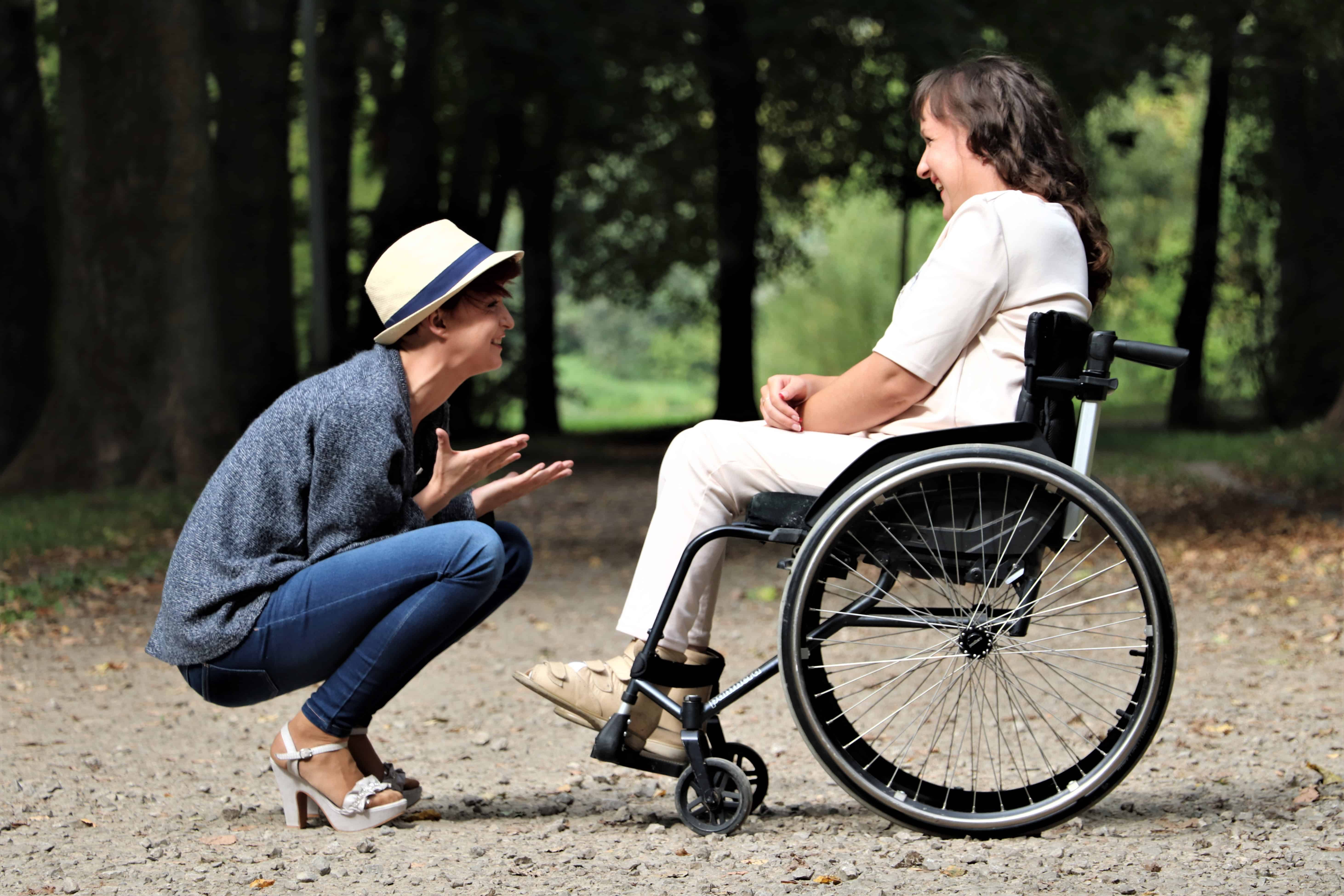 active adult in wheelchair talk to hiking tour guide