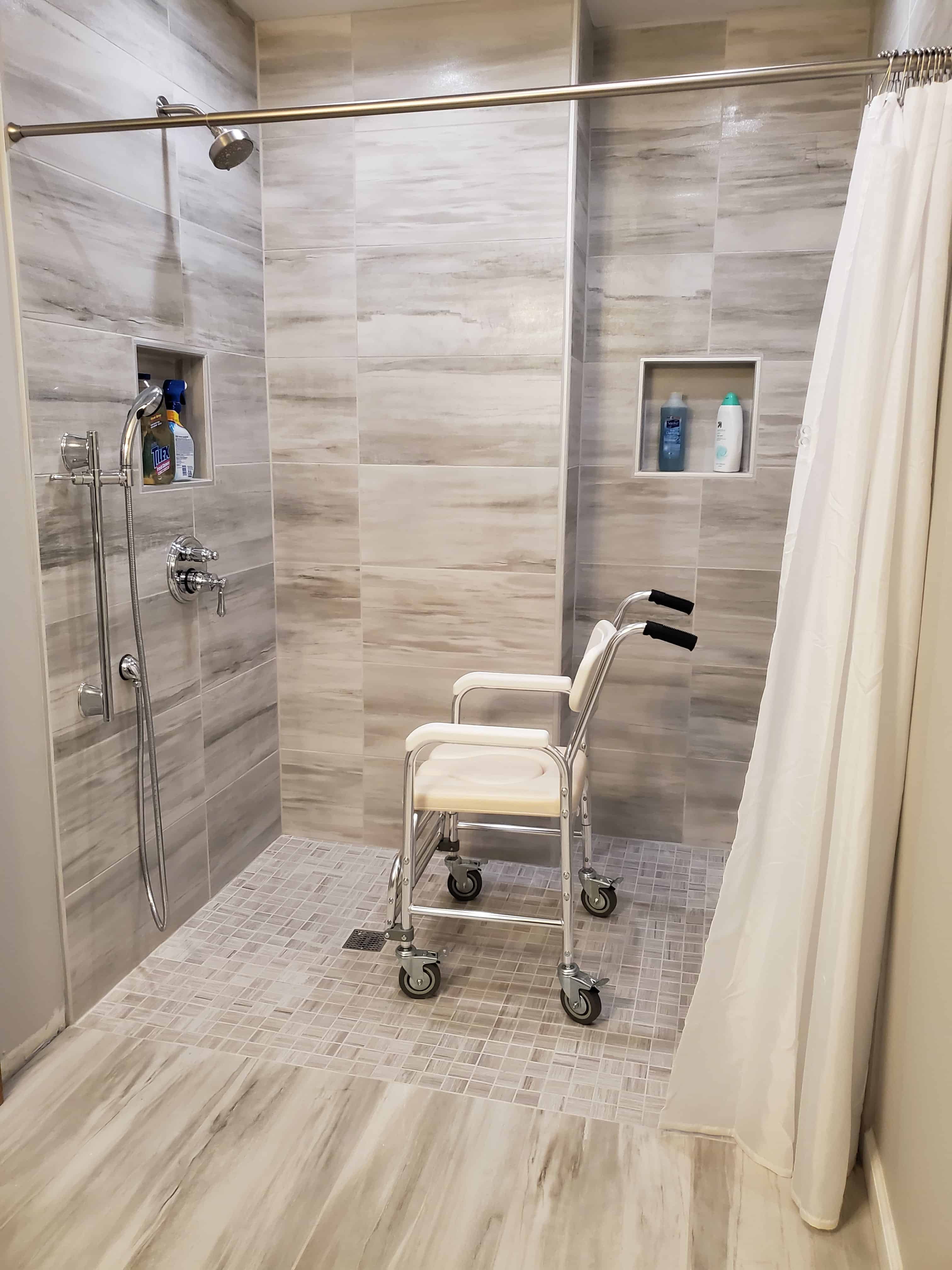 wheelchair accessible roll-in shower with shower chair in it