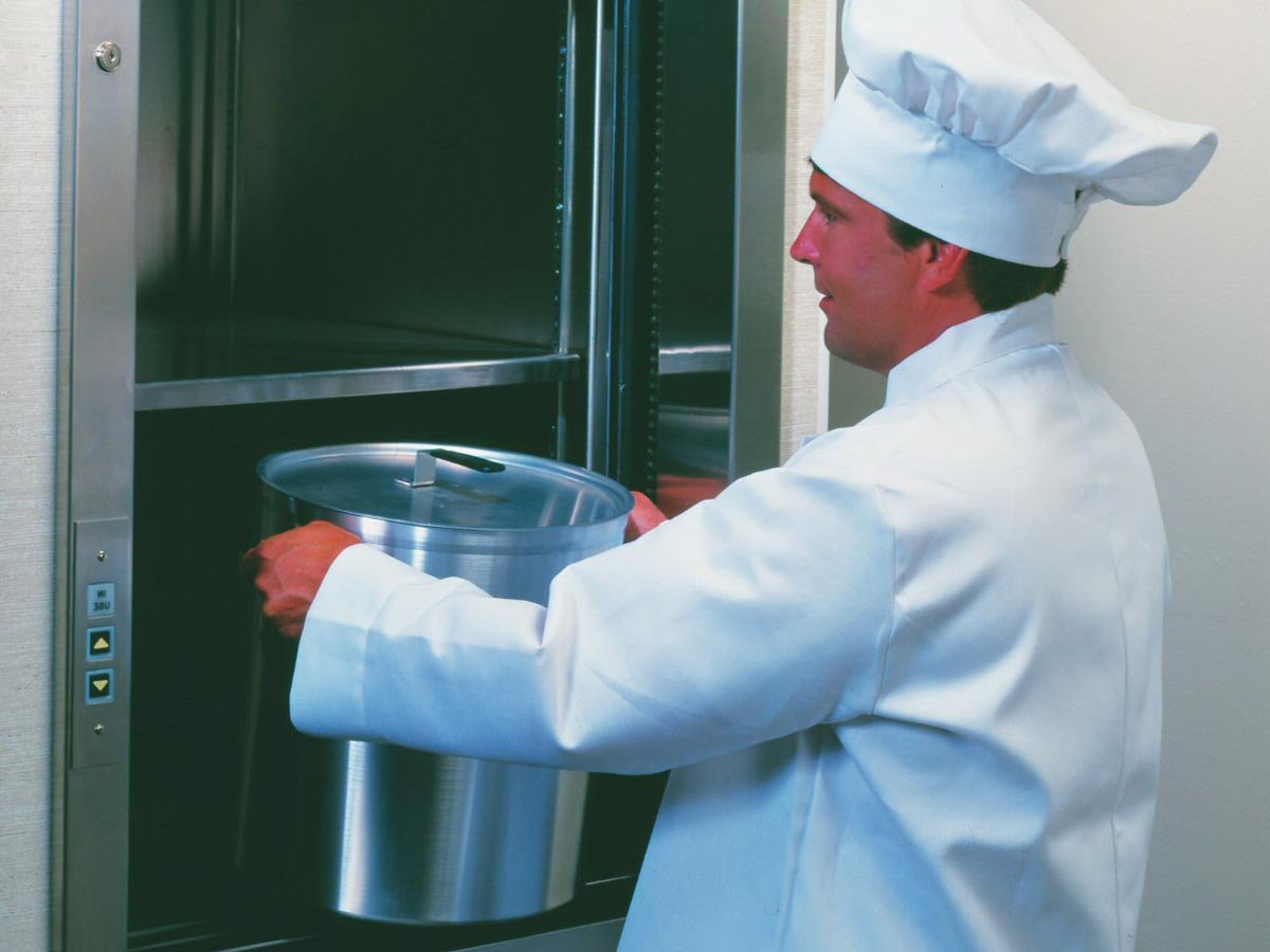 A chef putting a large pot into a commercial dumbwaiter