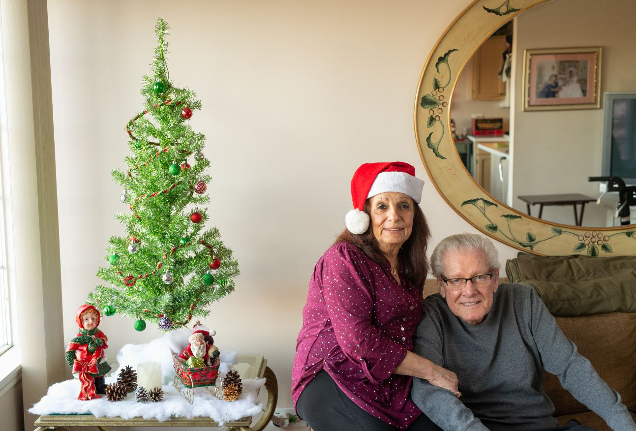 husband and wife sitting next to Christmas tree in living room