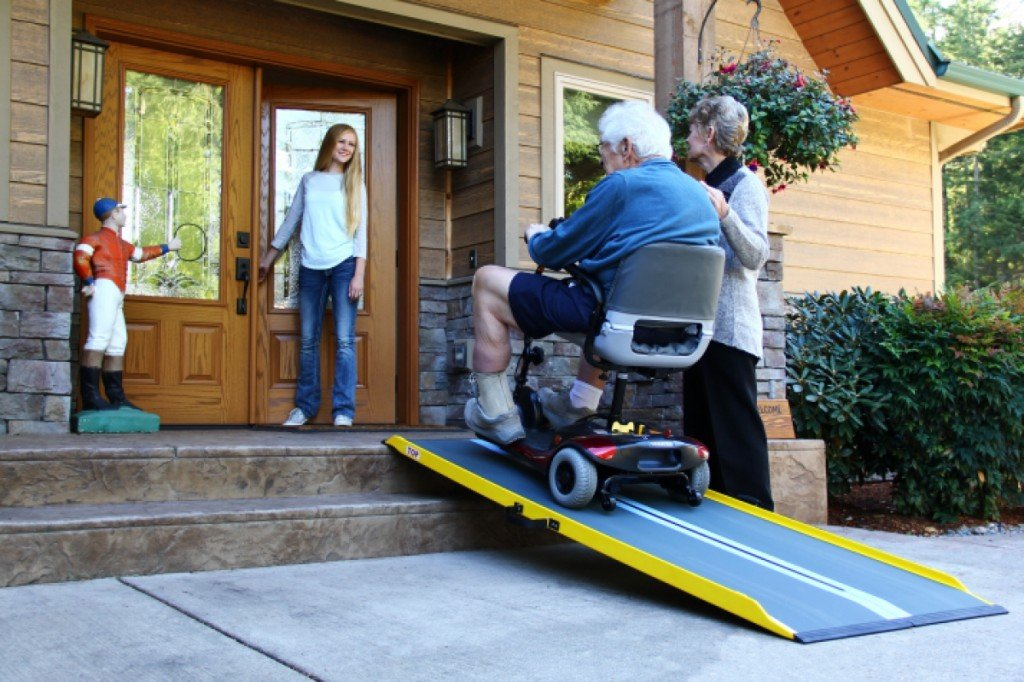elderly man in scooter using portable ramp to access front door of a house