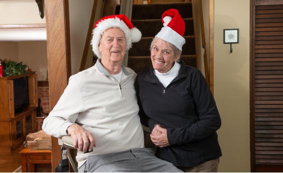 senior man and woman wearing Santa hats in home while man rides stairlift