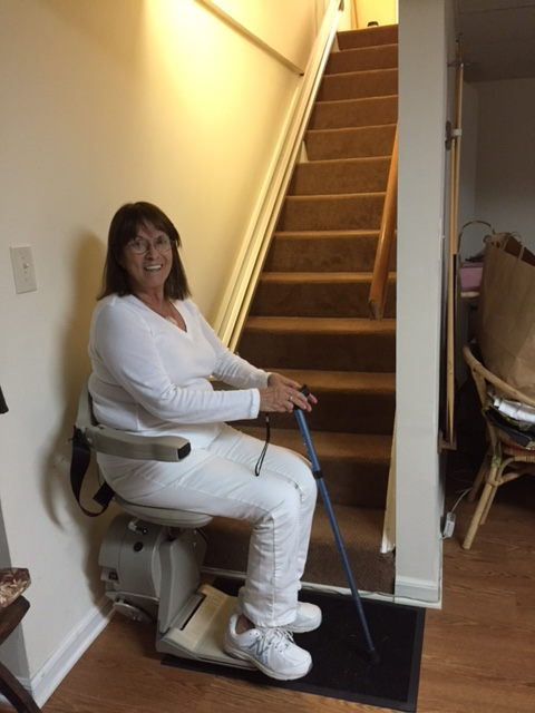 woman using stair lift to safely get down to the basement