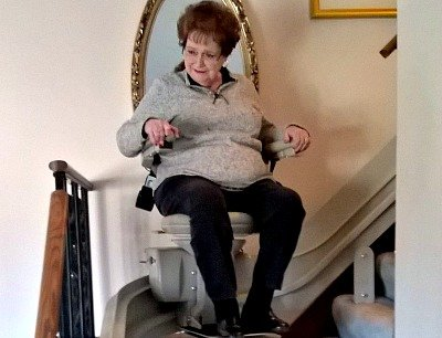 Woman riding a curved Bruno stair lift