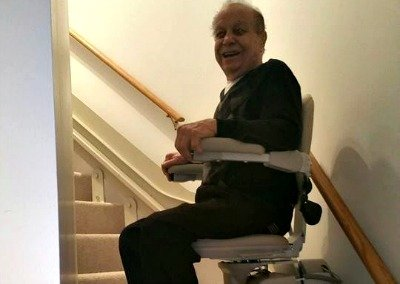 Man riding a curved Bruno stair lift at home