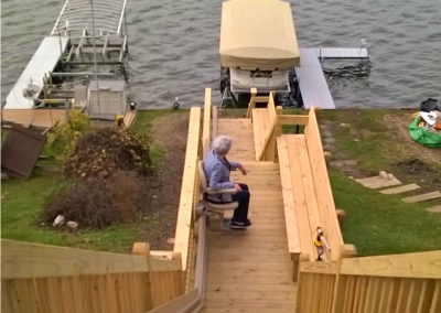 Woman riding a Bruno outdoor stair lift from her home to a dock