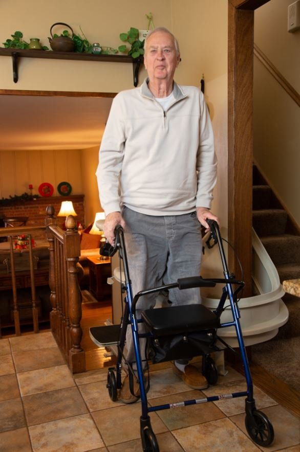 man holding onto walker for support as he gets out of stair lift chair