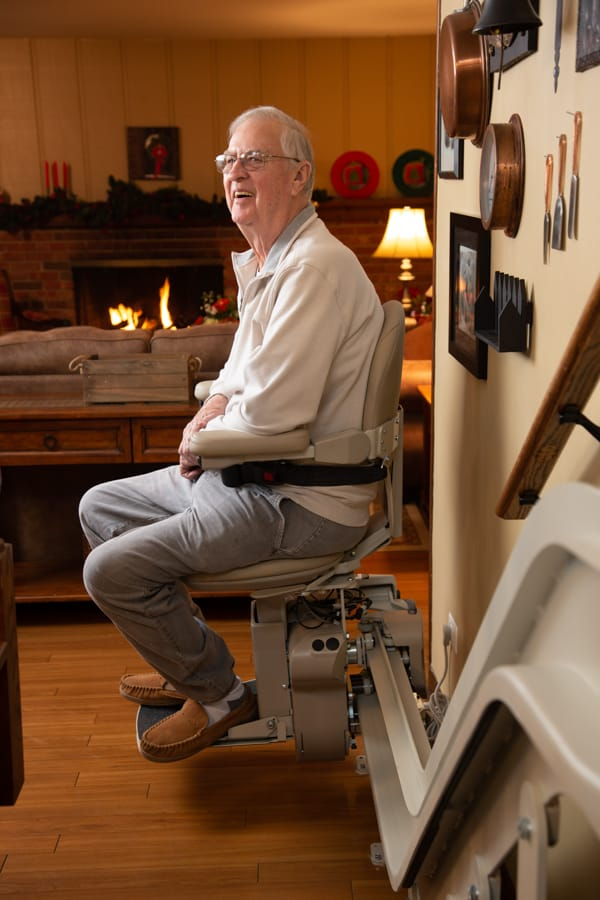 man smiling while sitting on stairlift in his home