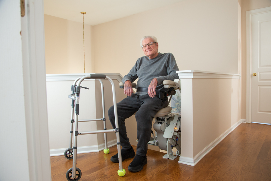 senior sitting on stairlift at top landing of stairs with walker in front of him on the landing