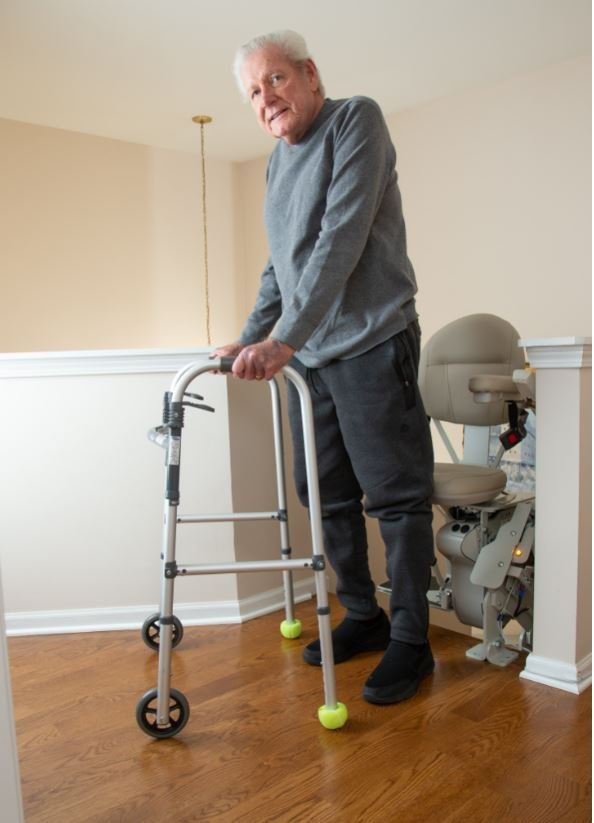 senior veteran using walker to safely get off of his stairlift at top level of his home