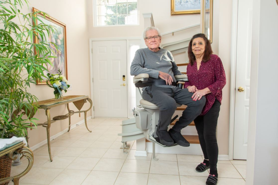 Lifeway Mobility customer riding curved stairlift in his home with his wife standing next to him