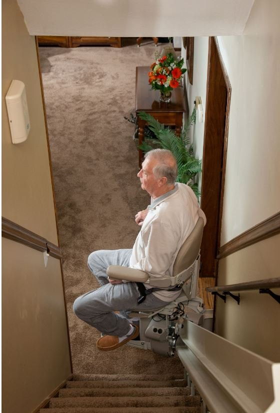man riding curved stair lift in home