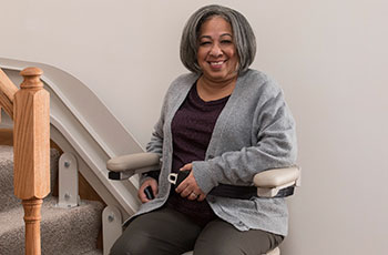 woman-fastens-seat-belt-before-using-stairlift-to-get-upstairs