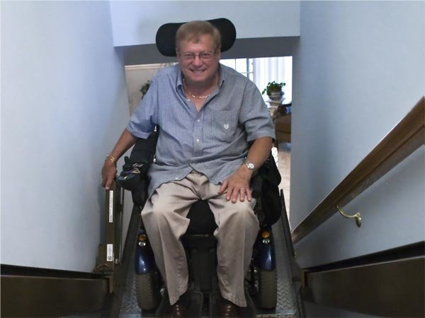 Man riding an incline platform wheelchair lift