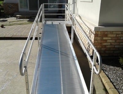 aluminum wheelchair ramp installed with handrails to provide easy access to front door of home in St. Charles, IL