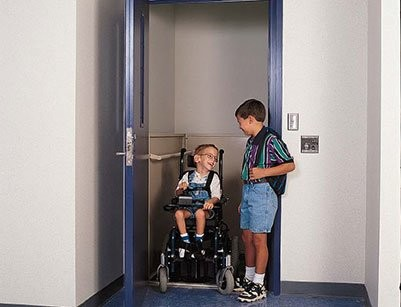 two-boys-getting-out-of-enclosed-commercial-wheelchair-lift-in-school