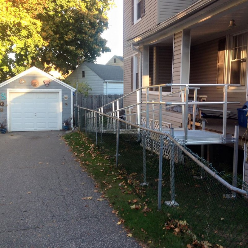 modular aluminum ramp inside fence of a two-story home