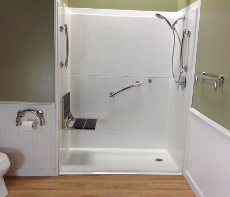 Renovative Bath Systems Barrier-Free Shower with grab bars, an adjustable shower head, and a fold-up bench
