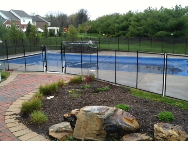 Protect A Child mesh pool fence with brick path