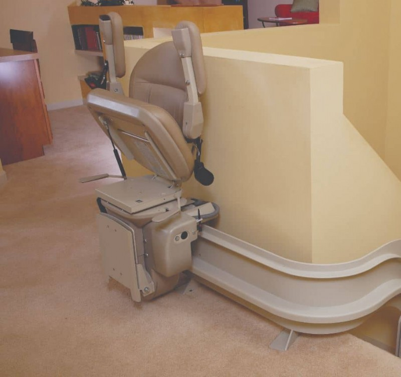 Bruno-Elite-Curved-stairlift-with-material-components-folded-up-at-top-landing.JPG