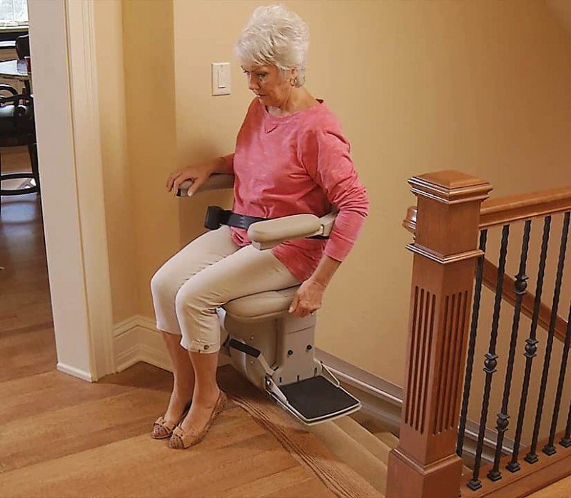 Bruno-Elite-Indoor-Straight-stairlift-with-lady-showing-swivel-seat-at-top-landing.jpg