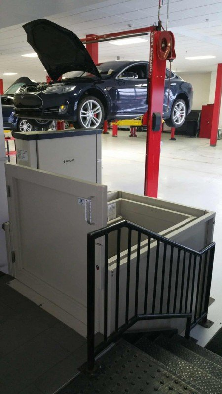commercial-wheelchair-lift-in-Tesla-Motors-service-center-with-Tesla-vehicle-in-background.jpg