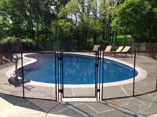 Pool fence built around residential pool in Indianapolis with a stone walkway