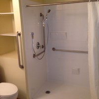 Renovative Bath Systems: Modular barrier-free shower with grab bars and an adjustable shower head