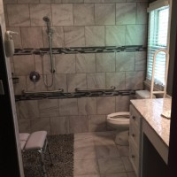Gray marble barrier-free shower with grab bars, an adjustable shower head, and a shower chair/bench