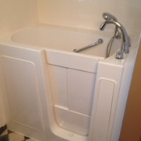 Best Bath brand walk-in tub with grab bars and solid white door, closed