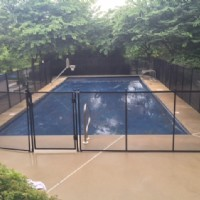 Protect A Child mesh pool fence around a shaded rectangular pool