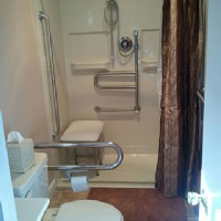 handicap-shower-installation-with-pivot-grab-bars-in-wall-shower-niche-and-shower-bench