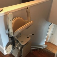 stair-lift-with-components-folded-up-at-top-landing-of-stairs-in-Havervill-Massachuetts.jpg