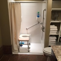wheelchair-accessible-shower-with-shower-chair-and-grab-bars-in-Indiana-home.jpg