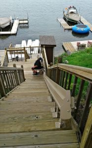 Image of a man riding down a stair lift that was installed on the stairs in his backyard in Round Lake, Illinois
