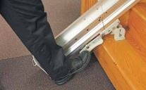 Image of a man's foot on the folding rail's foot lock