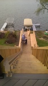 Image of a woman riding her new outdoor stair lift that was installed on the stairs in the backyard of her home in Wonder Lake, Illinois